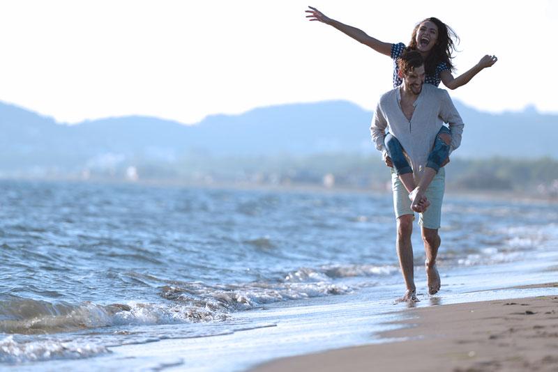 healthy couple walking on beach